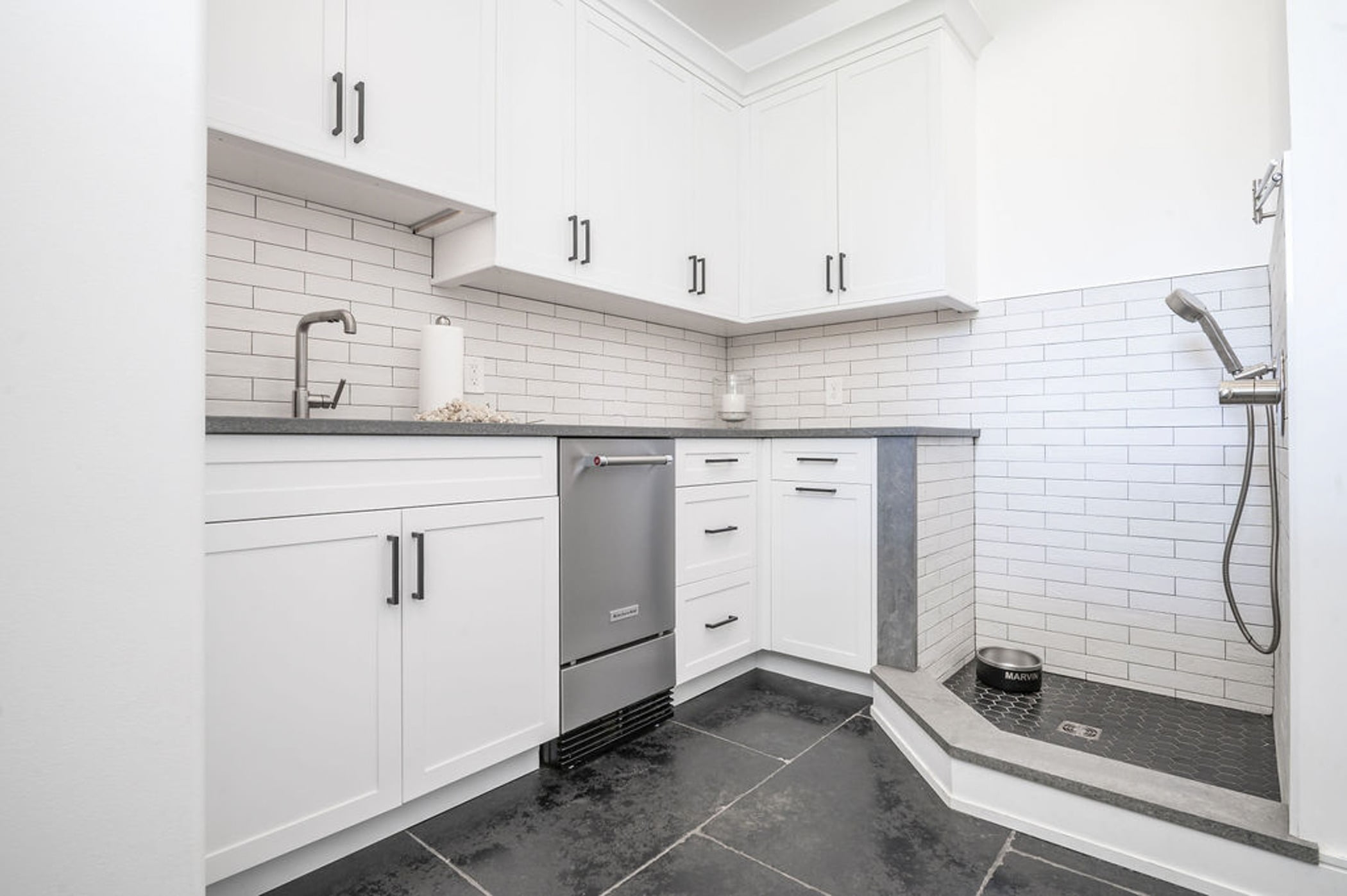 Remodeled mudroom with a kitchenette, white cabinetry, gray countertops and a small dog shower with honeycomb and subway tile