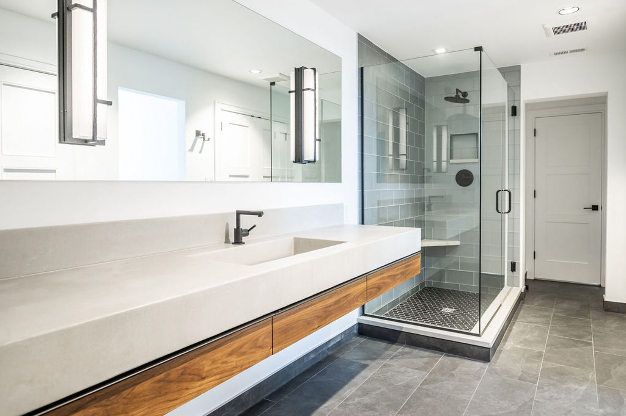 Modern style bathroom with marble countertops with wood trim, and an all glass shower lined with grey tiles