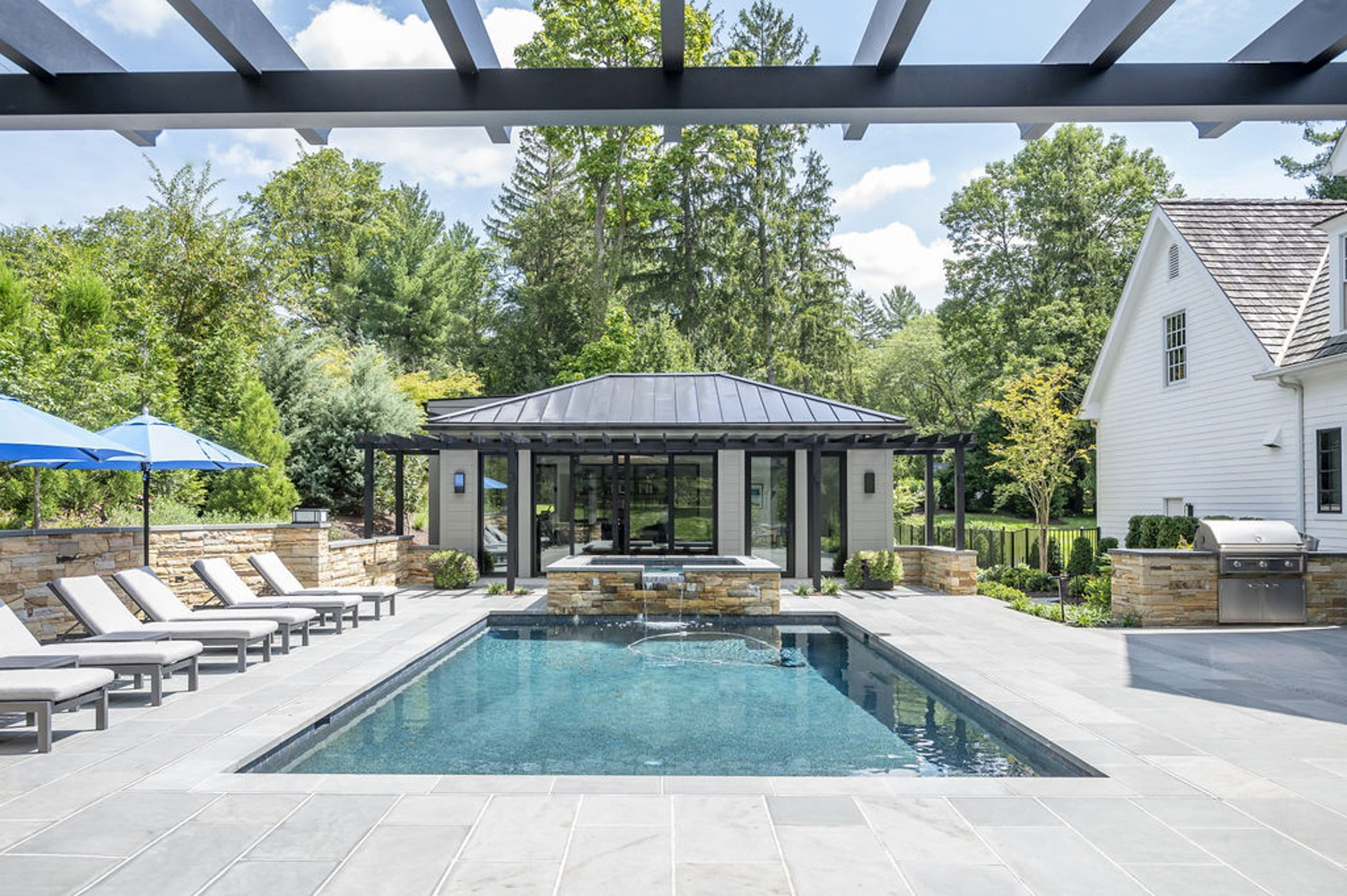 Transitional backyard patio and poolhouse with concrete pavers and cobblestone accented retaining walls and hot tub