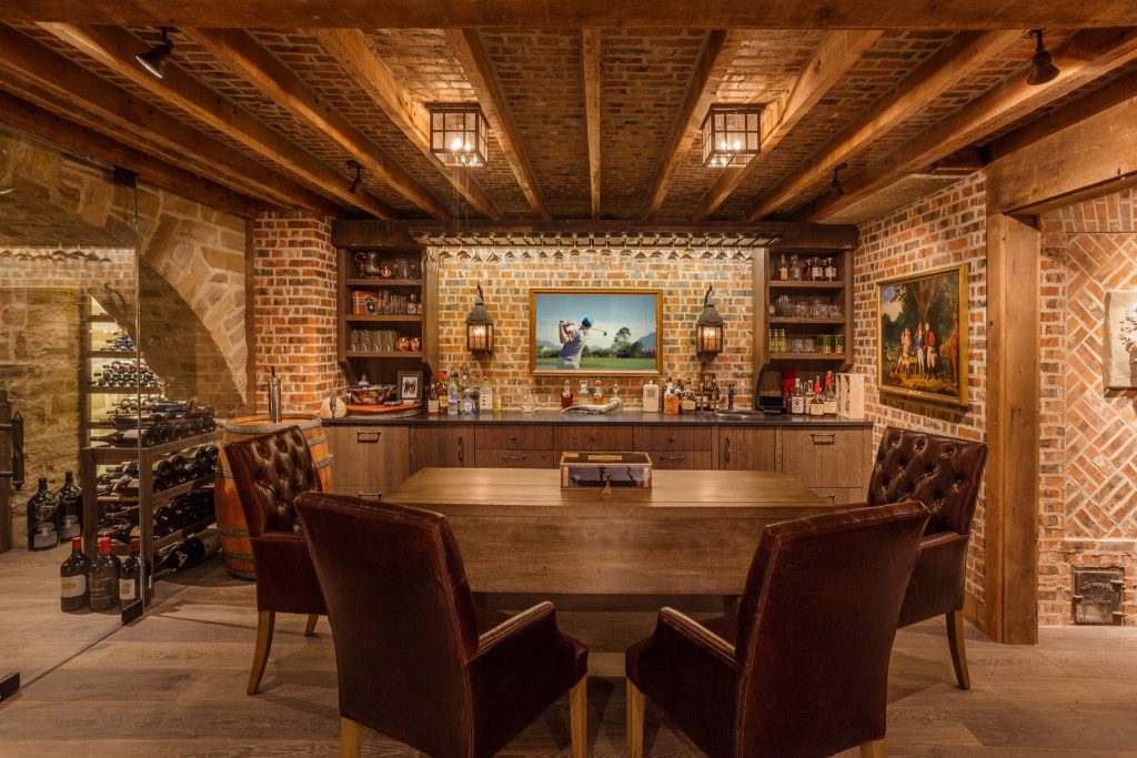 Rustic style brick cellar/basement/bar with fine leather chairs around a wood table