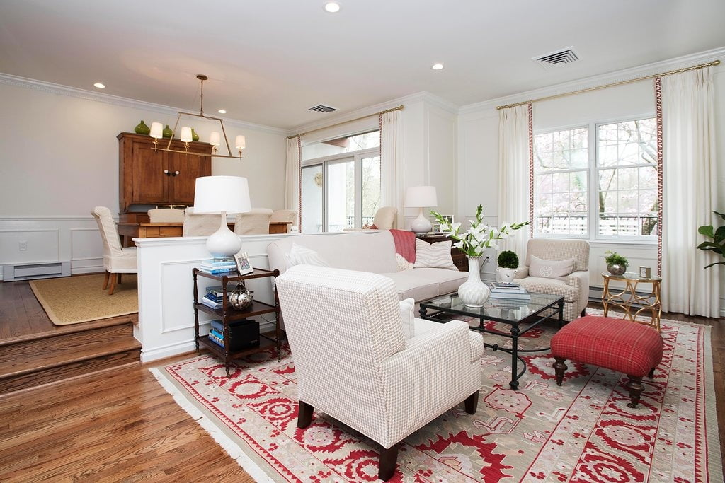 Transitional living and dining rooms with medium hardwood flooring, minimal cream furniture, and patterned carpet accented red
