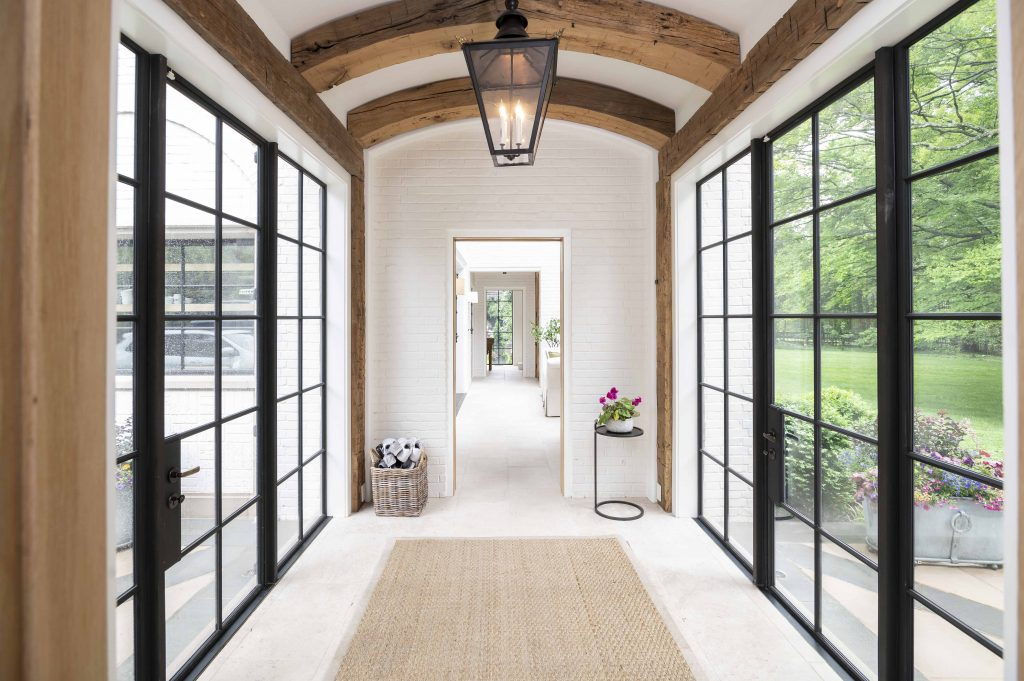 Contemporary/modern hallway with thick wooden ceiling arches, white tile flooring, and black steel framed doors and windows on either side